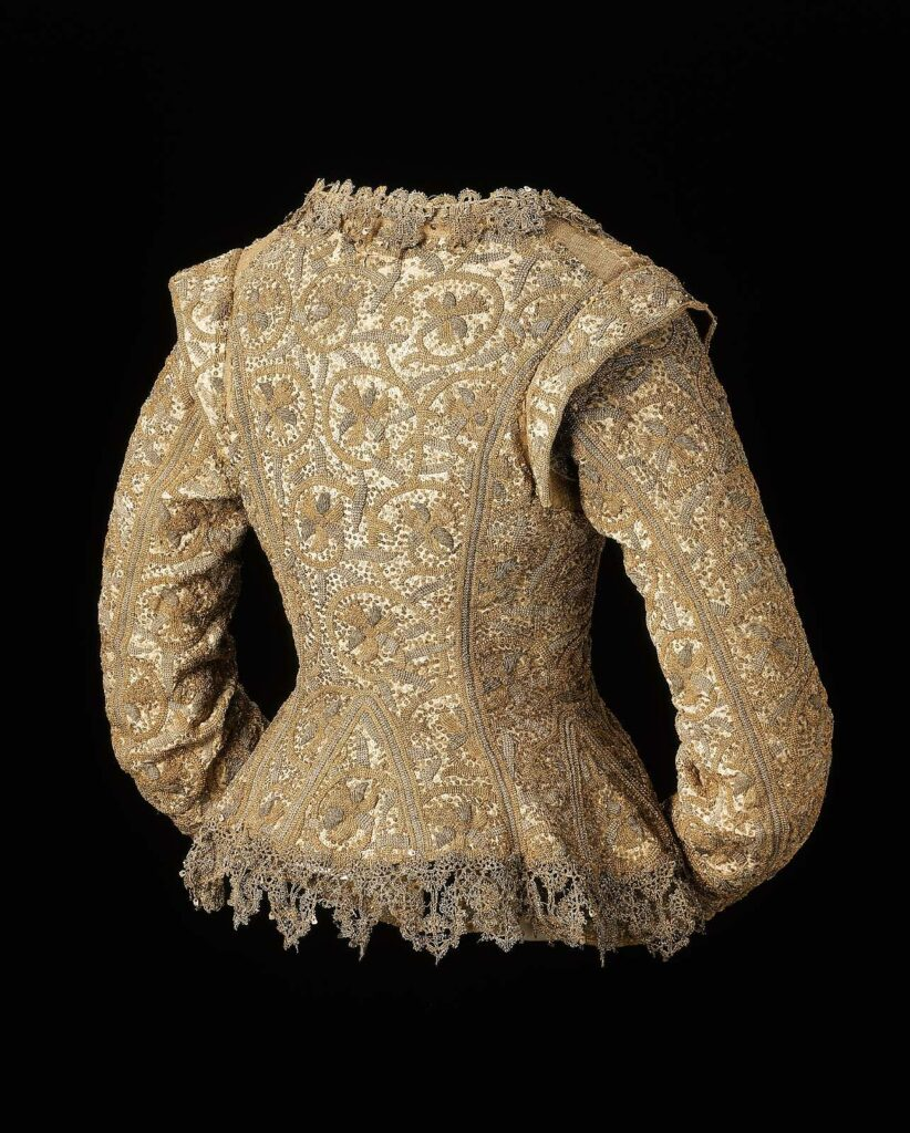 English woman's jacket in undyed linen embroidered with silver and gilt-silver yarns and spangles in daffodil scroll pattern, trimmed with metallic lace.